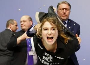 La conferenza stampa di Mario Draghi è stata interrotta per pochi minuti dopo che una manifestante ha assalito il governatore della banca centrale.