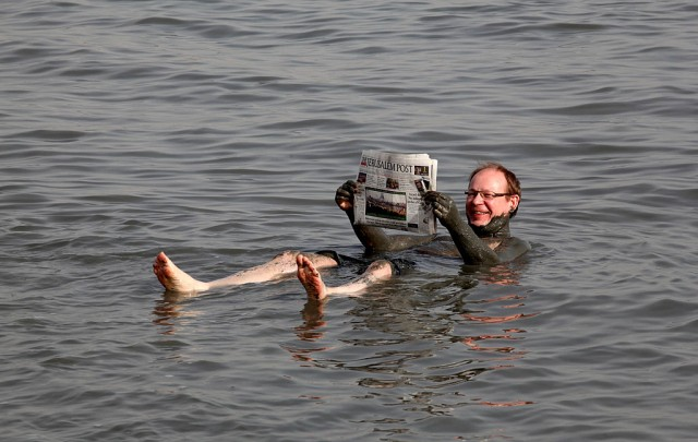 A European tourist reads a newspaper as he bathes in the Dead Sea on a sunny day with a temperature of 25 Celsius degrees (77 F) in Kalya on February 12, 2010.  AFP PHOTO/GALI TIBBON (Photo credit should read GALI TIBBON/AFP/Getty Images)