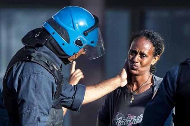 Un poliziotto consola una delle rifugiate vittima degli scontri con le forze dell'ordine a Piazza Indipendenza