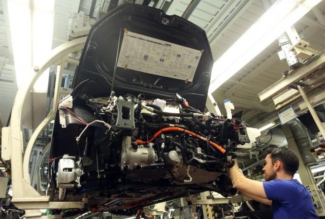 Un operaio al lavoro su un modello di Golf Volkswagen nella fabbrica di Wolfsburg