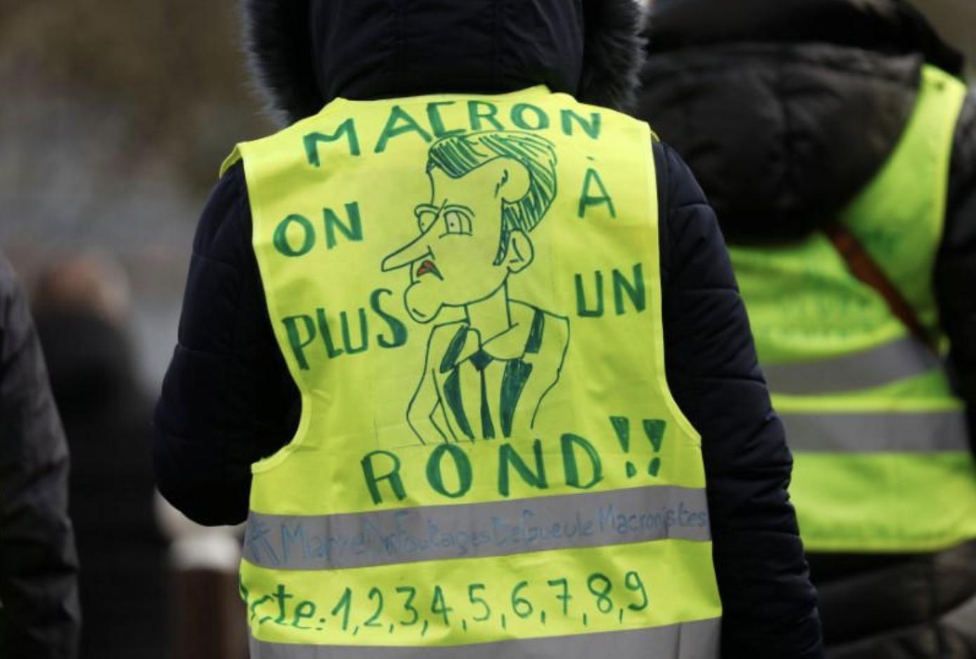 """Protesta a Creteil, vicino a Parigi, di uno dei manifestanti che indossano i gilet gialli e che chiedono interventi per aumentare il potere di acquisto: lo slogan recita """"Macron, siamo al verde"""""""